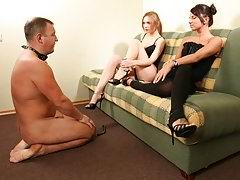 Two sexy dommes take turns to fuck slave in the ass with a massive strap-on