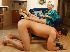 Slave kissing mistress's charming feet while she's walking along the room