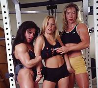 During a long day of lifting weights and spotting each other Kristy, Cinder, and April take it to the bedroom where they fuck each other with strapons and double ended dildos.
